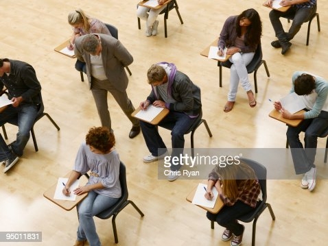 Professor walking by college students taking test in classroom