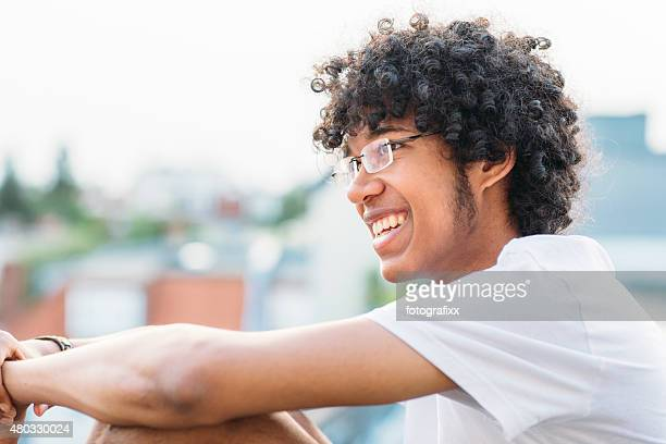 profil young man with afro in front of urban background