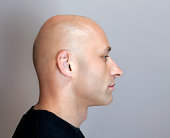 Profile headshot of a bald man with his eyes closed