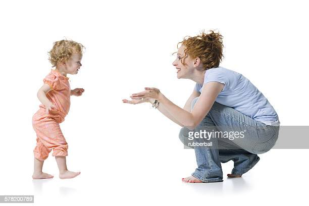 Profile of a baby girl reaching for her mother