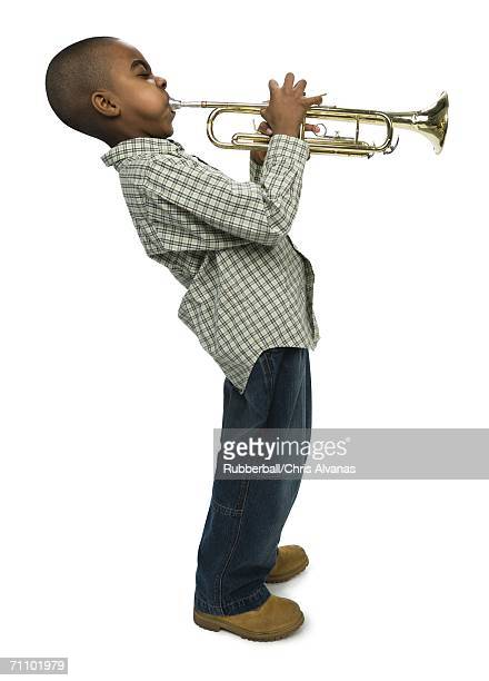 Profile of a boy blowing a trumpet