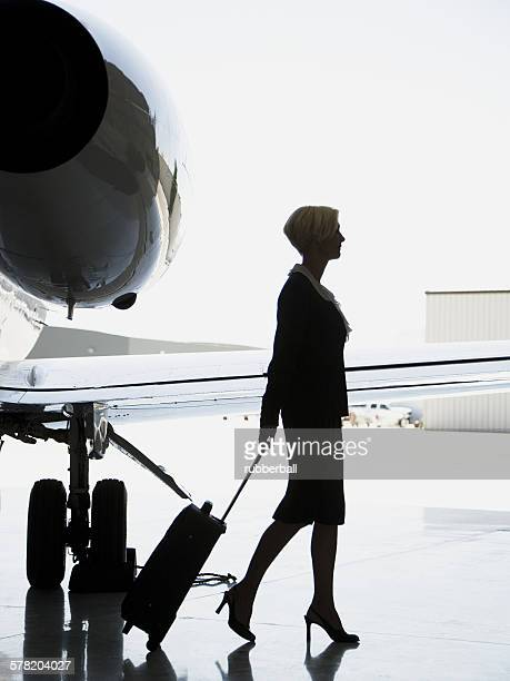 Profile of a businesswoman pulling a suitcase