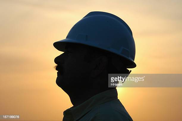 A profile of a construction worker in silhouette