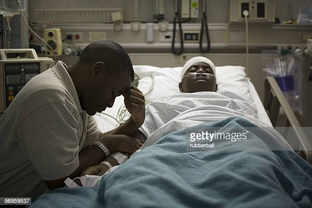 Profile of a father sitting beside his son lying on a hospital bed