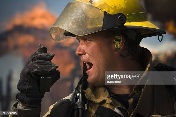 Profile of a firefighter using a walkie-talkie