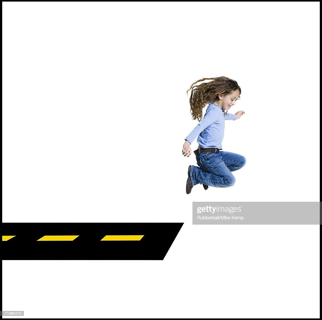 Profile of a girl jumping off the road : Stock Photo