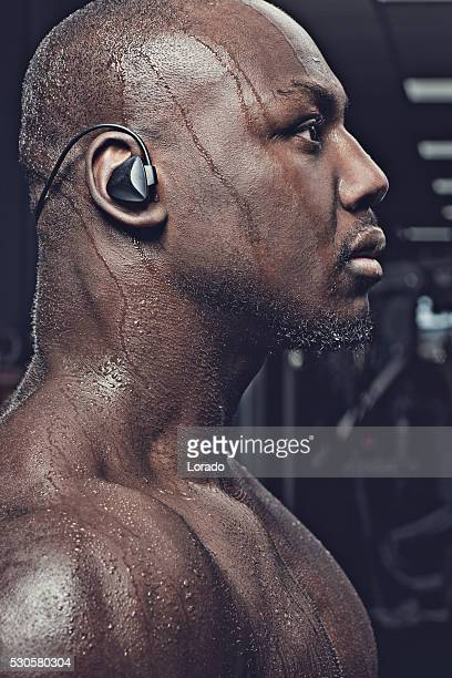 Profile of a handsome muscled black male exercising in gym