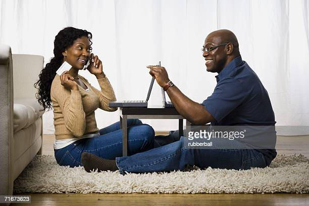 Profile of a mature woman talking on a mobile phone with a man sitting in front of her