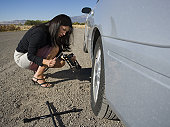 Profile of a mid adult woman repairing her car