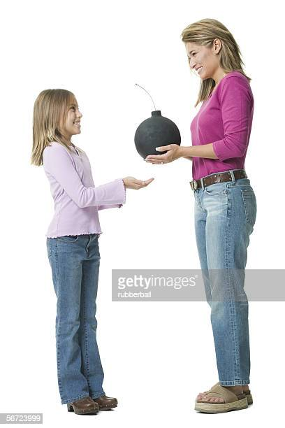 Profile of a mother giving a bomb to her daughter