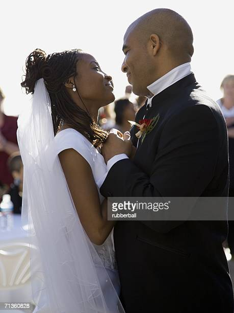 Profile of a newlywed couple holding hands and looking at each other