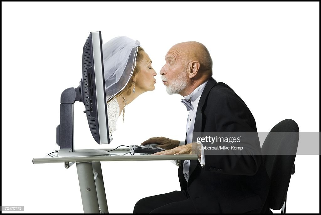 Profile of a senior man kissing a senior woman emerging from a computer monitor : Stock Photo
