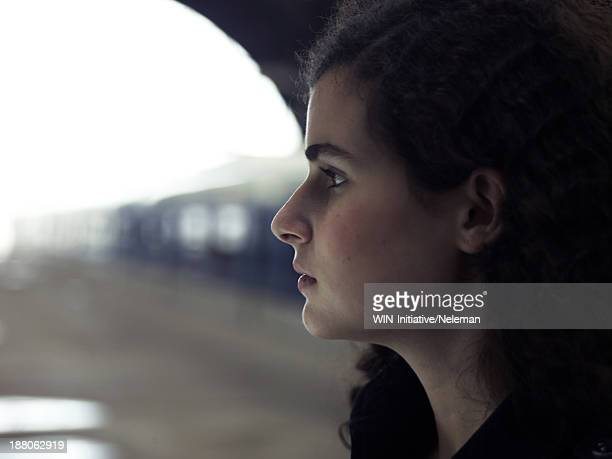 Profile of a teenage girl at a train station