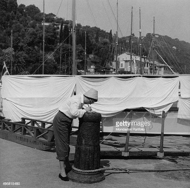 Profile of a tourists wearing a cap and fisherman's pants who signs a postcard on a stone bollard at the dock on the background main masts of the...