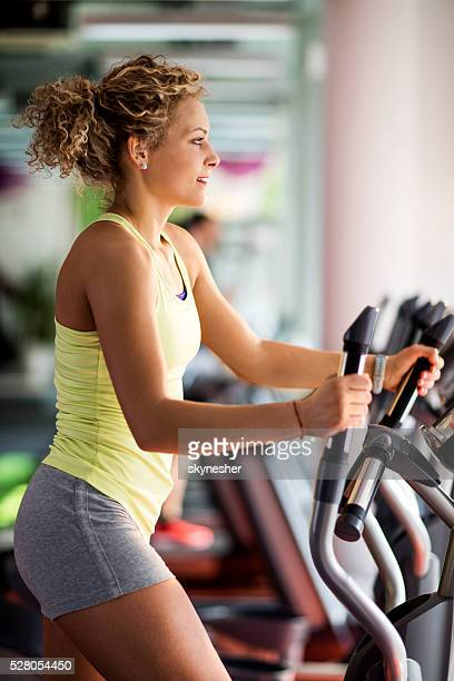 Profile of a woman exercising in gym on cross trainer.