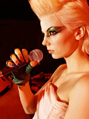 Profile of a Young Female Punk Singer With Exaggerated Eye Make-Up and a Blonde Quiff Holding a Microphone