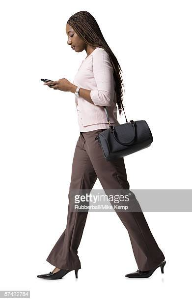 Profile of a young woman walking and using a mobile phone