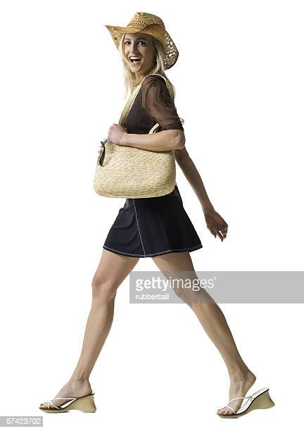 Profile of a young woman walking with a hand bag