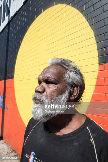 Profile of aboriginal man with grey hair and beard wearing black t shirt in front of a brick wall painted with aboriginal flag