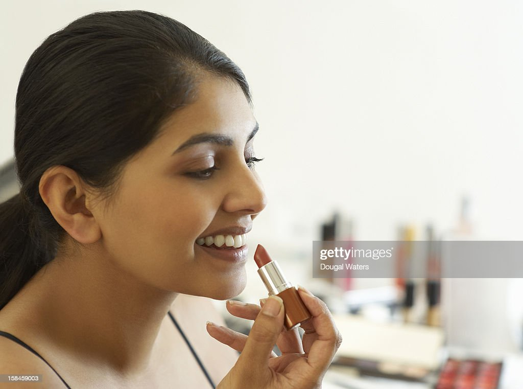 Profile of Asian woman applying lipstick. : Stock Photo