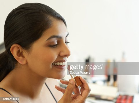 Profile of Asian woman applying lipstick. : Stock Photo