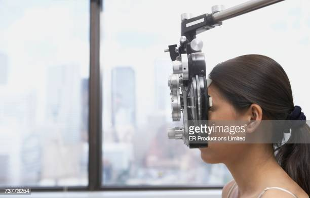 Profile of Asian woman's face behind ophthalmology equipment