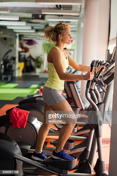 Profile of athletic woman exercising on stair climbing machine.