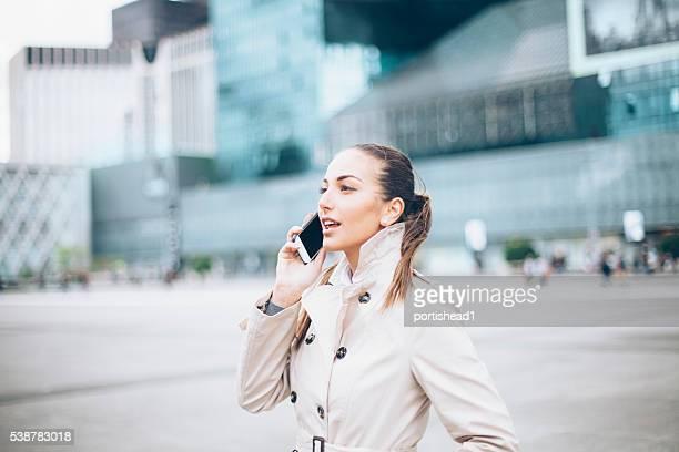 Profil de la Jolie jeune femme parlant au téléphone dans la rue