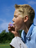 Profile of boy blowing bubbles.