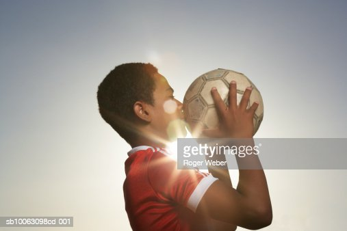 Profile of boy (12-13) kissing football, lens flare