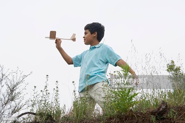 Profile of boy throwing wood airplane