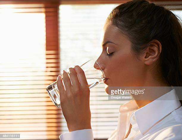 Profile of business woman drinking glass of water