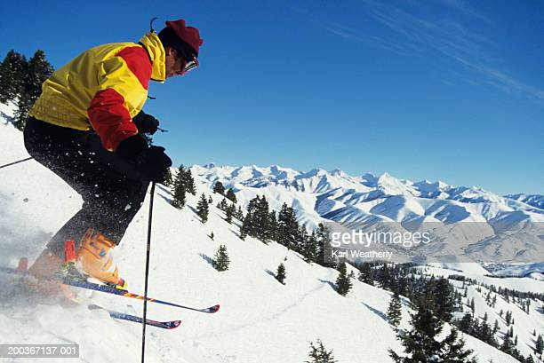 Profile of downhill skier, snow-capped mountains behind, Idaho, USA