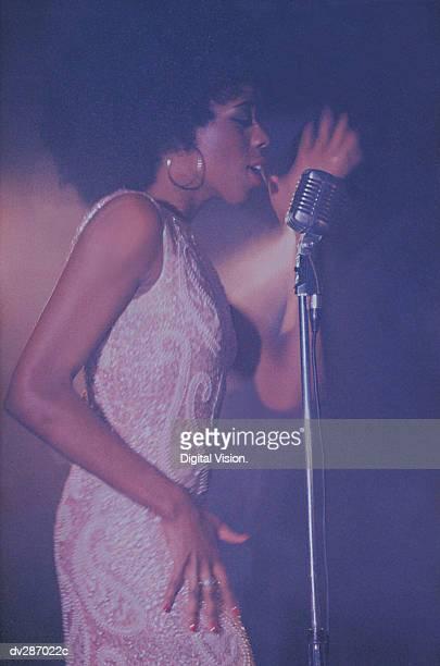 Profile of female vocalist singing, eyes closed