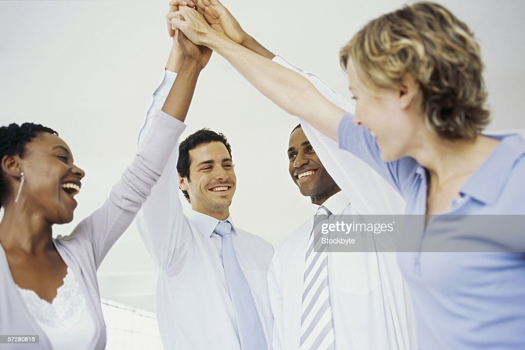 Profile of four businesspeople celebrating with high fives. : Stock Photo