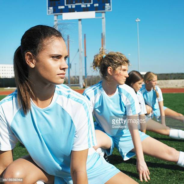 profile of four female soccer players (16-18) stretching