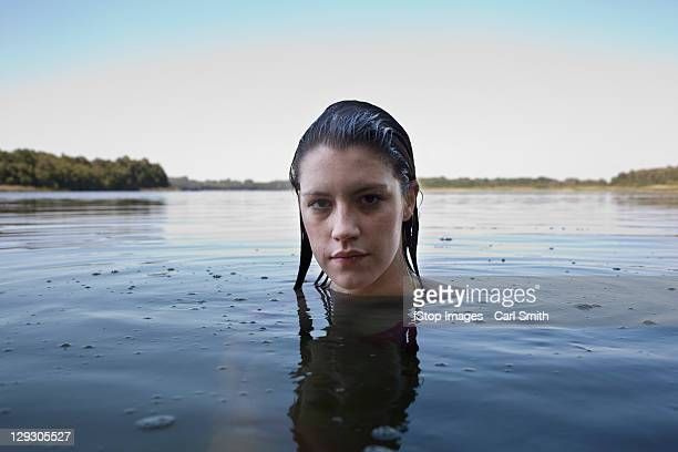 Profile of girl with head above water looking at camera