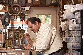 Profile of man fixing clock in repair shop