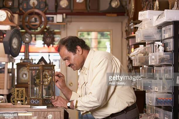 Profile of man fixing clock in repair shop