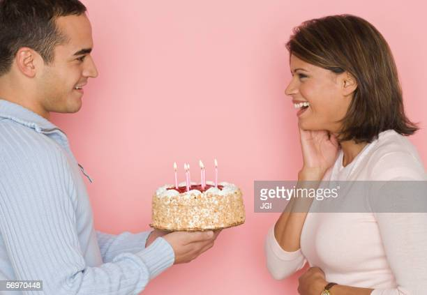 Profile of man holding cake and looking at woman