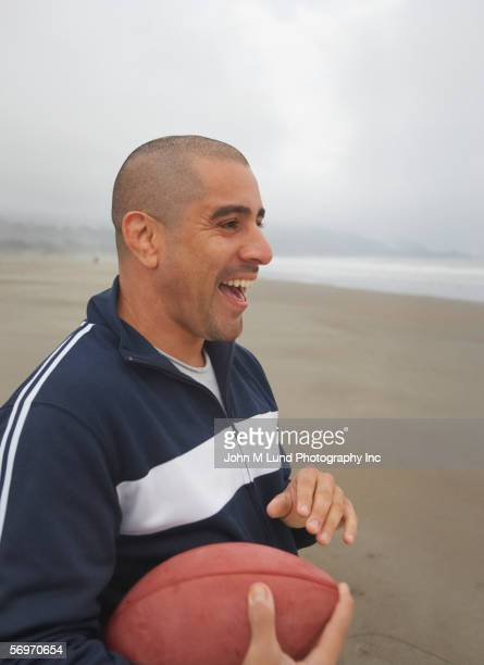 Profile of man holding football and laughing