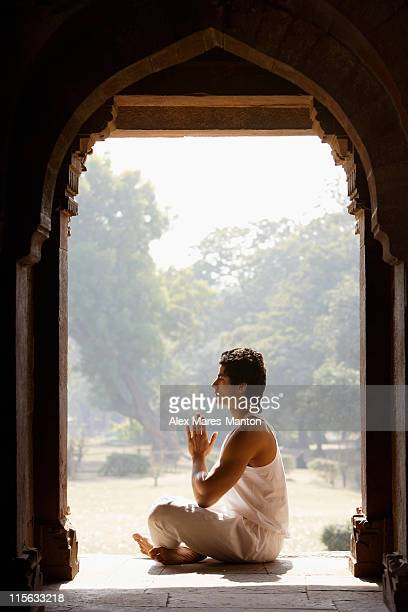 Profile of man in yoga posture sitting in ancient monument