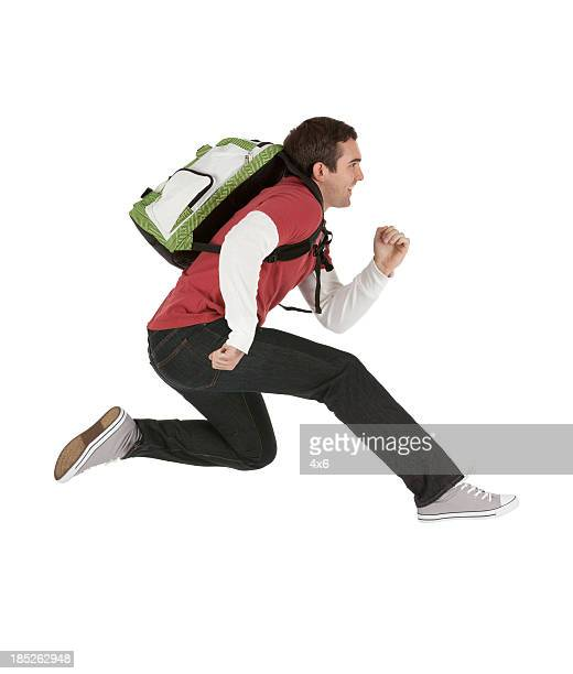 Profile of man running with a backpack