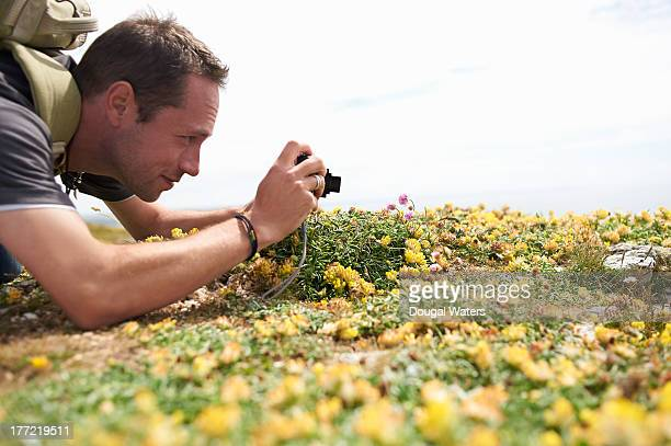 Profile of man taking picture of flower.
