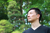 profile of middle aged Japanese man outdoors
