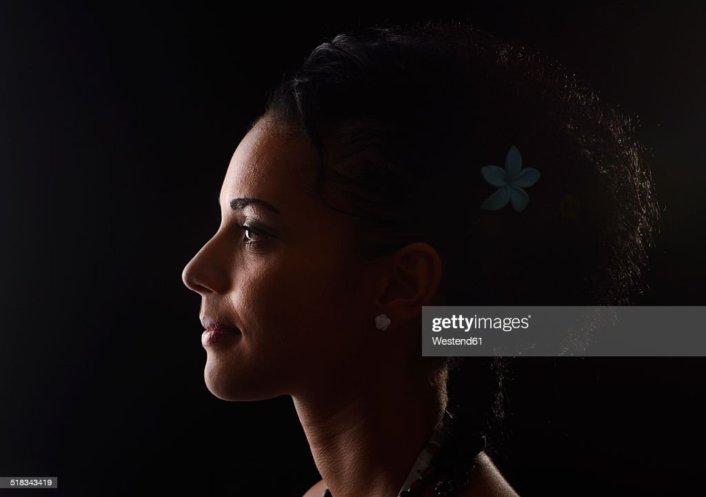 Profile of smiling young woman in front of black background