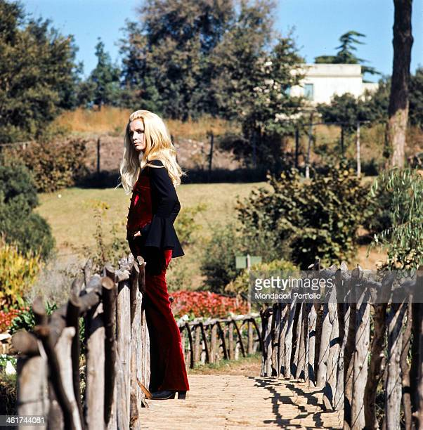 Profile of the welldressed Italian singer Patty Pravo born Nicoletta Strambelli standing on a wooden bridge wearing an elegant red velvet suit along...