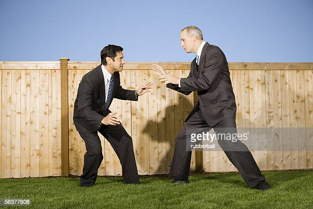 Profile of two businessmen playing and rough housing