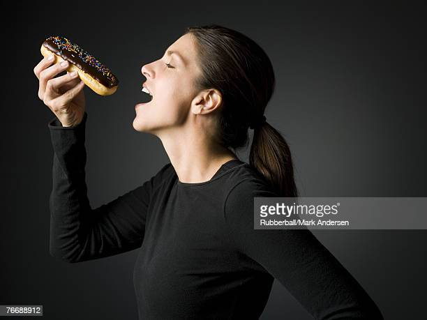 Profile of woman eating an eclair donut