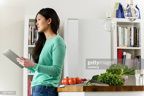 Profile of woman holding digital tablet leaning against table